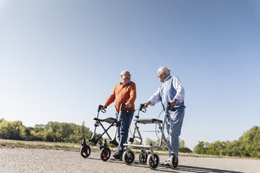 Two old friends walking on a country road, using wheeled walkers - UUF15525