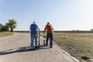 Two old friends walking on a country road, using wheeled walkers - UUF15528