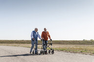 Two old friends walking on a country road, using wheeled walkers - UUF15531