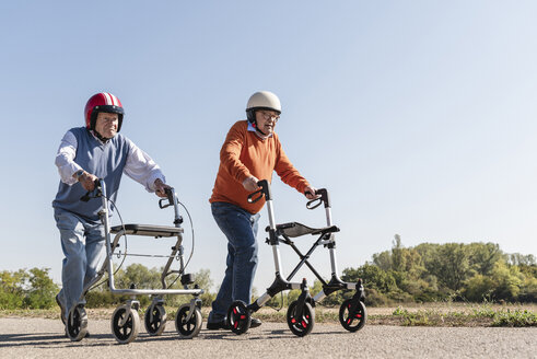 Two old friends wearing safety helmets, competing in a wheeled walker race - UUF15537