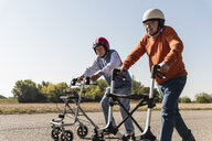 Two old friends wearing safety helmets, competing in a wheeled walker race - UUF15546