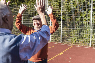 Two fit seniors high fiving on a basketball field - UUF15549