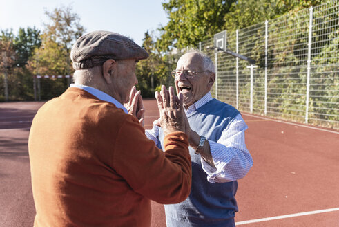 Two fit seniors high fiving on a basketball field - UUF15552