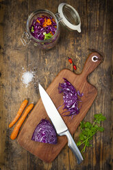 Homemade red cabbage, fermented, with chili, carrot and coriander, preserving jar on wood - LVF07485