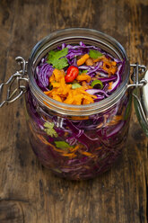 Homemade red cabbage, fermented, with chili, carrot and coriander, preserving jar on wood - LVF07488