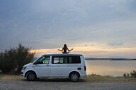 woman meditating on top of the van at sunset on the lake - SKCF00540