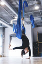 Full length of young woman practicing aerial yoga while hanging from hammock in gym - CAVF49996