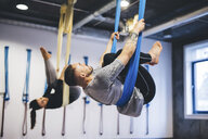 Friends hanging on hammocks while practicing aerial yoga in gym - CAVF49999