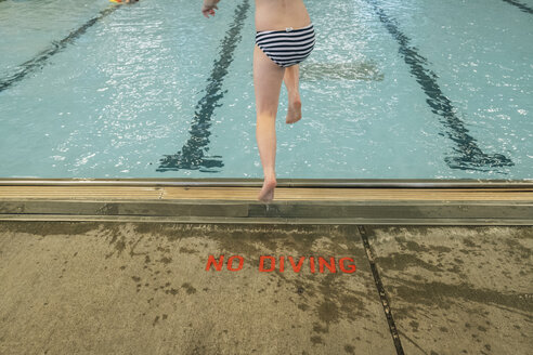 Low section of girl wearing striped underwear while diving into swimming pool - CAVF50020
