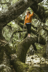 Young woman standing on mossy branch at rainforest - CAVF50041
