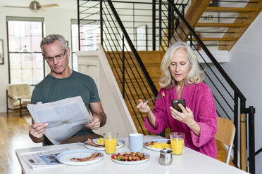 Man reading newspaper while woman using smart phone at dining table - CAVF50062