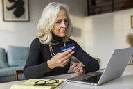 Senior woman using laptop computer while paying bills at home - CAVF50077