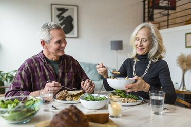 Smiling couple having lunch at dining table - CAVF50086
