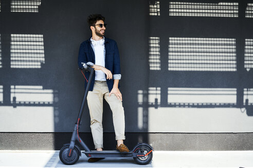 Smiling man with electric scooter outdoors - BSZF00761