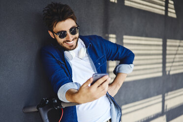 Portrait of smiling young man with electric scooter looking at cell phone - BSZF00764