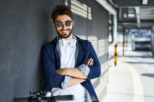 Portrait of smiling man wearing sunglasses and headphones - BSZF00767
