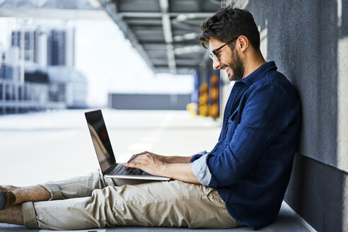 Smiling young man sitting on the ground using laptop - BSZF00773