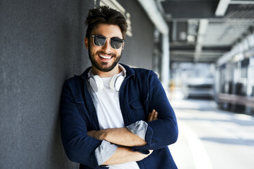 Portrait of smiling young man wearing sunglasses leaning against wall - BSZF00782