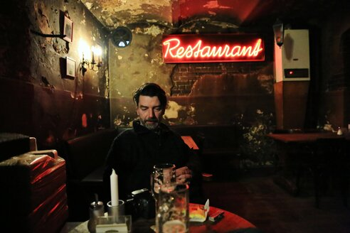 Man in dingy restaurant with beer - INGF02517