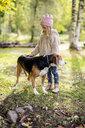 Little girl stroking dog in autumnal garden - PSIF00123