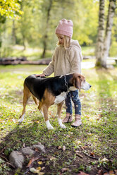 Little girl stroking dog in autumnal garden - PSIF00123