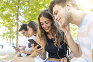 Group of friends at a park having fun together and listening to music on cell phones - WPEF00925