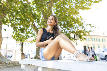 Smiling young woman relaxing on a bench at park listening to music - WPEF00931