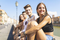 Italy, Pisa, group of four happy friends sitting on a wall along Arno river - WPEF00940