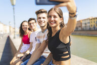 Italy, Pisa, group of four happy friends sitting on a wall along Arno river taking a selfie - WPEF00943
