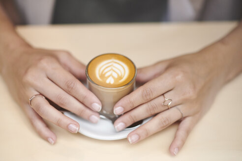Hands of woman holding coffee cup - LUXF01265