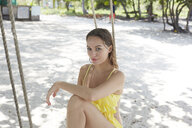 Young woman wearing yellow on beach swing - LUXF01391