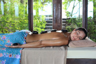Young woman getting lastone therapy on her back - LUXF01400