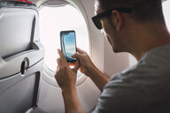 Man in airplane, using smartphone, taking a picture, airplane window - KKAF02463