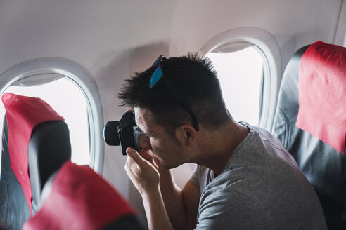 Man taking a picture in airplane - KKAF02466