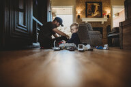 Surface level image of father and son playing with toy cars on floor at home - CAVF50097