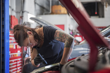 Female tattooed mechanic examining car engine in auto repair shop - CAVF50103