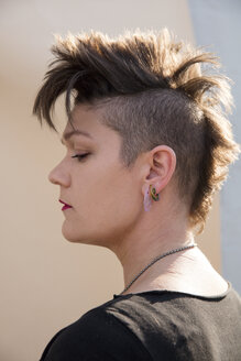 Side view of hipster woman with spiky hair against backdrop - CAVF50115