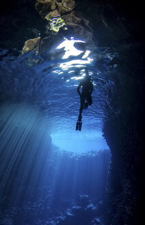 Low angle view of silhouette woman snorkeling undersea - CAVF50127