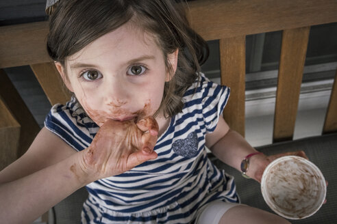 High angle portrait of girl with messy mouth eating chocolate while sitting on chair at home - CAVF50163