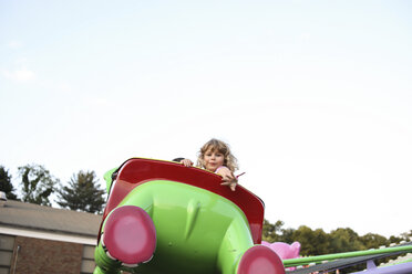 Low angle portrait of cute girl sitting on carousel car against sky at amusement park - CAVF50196