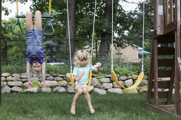 Girl hanging upside down while sister swinging at playground - CAVF50205