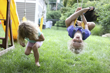 Playful sisters swinging over grassy field at playground - CAVF50208