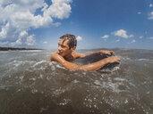 Shirtless teenage boy looking away while surfing on sea against blue sky - CAVF50211