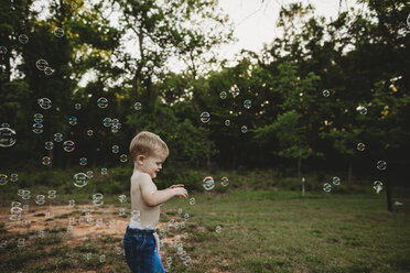 Side view of shirtless baby boy playing with bubbles while standing at park - CAVF50226