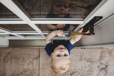 High angle portrait of cute baby boy opening door - CAVF50229