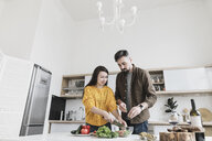 Couple preparing salad together in modern kitchen - KMKF00579