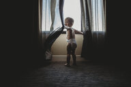 Rear view of shirtless baby boy playing with curtains while standing by window at home - CAVF50309