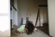 Boy laughing while lying on rug at home - CAVF50312