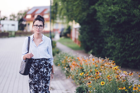 Portrait of young woman carrying purse while standing by flowering plants at park - CAVF50318