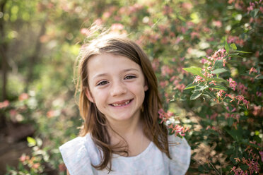 Close-up portrait of happy girl standing by plants at park - CAVF50324